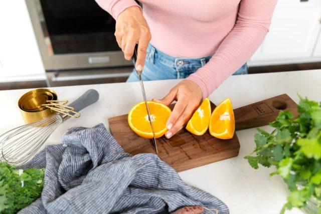 Woman Cutting Oranges in Kitchen